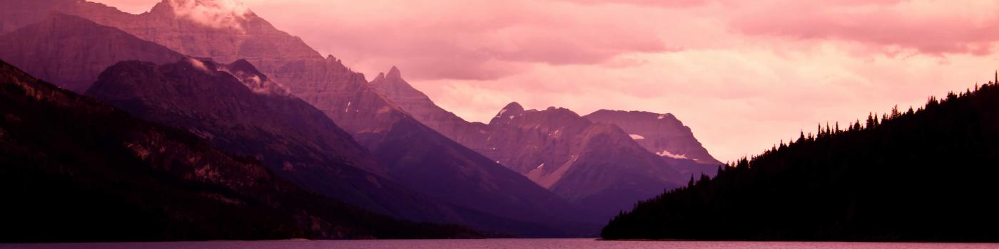 mountains rising above a lake with purple lighting