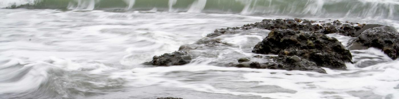 Wave breaking on rocks and pebble beach