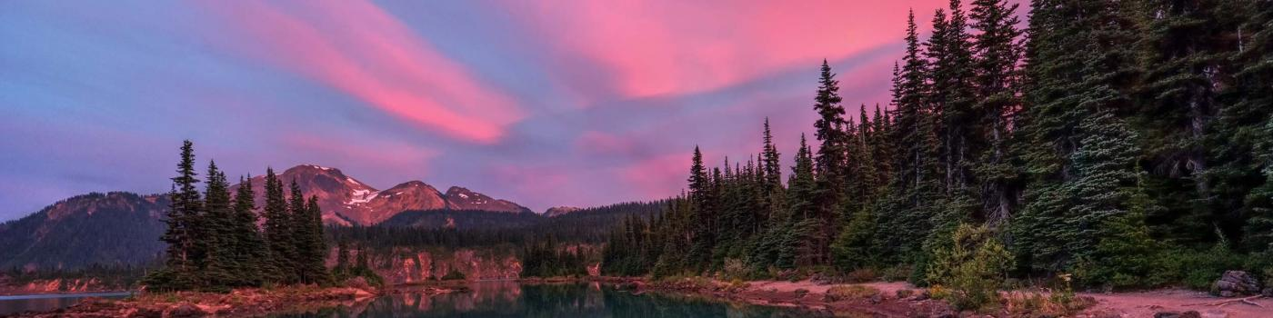 Pink sunset reflected over lake and mountains