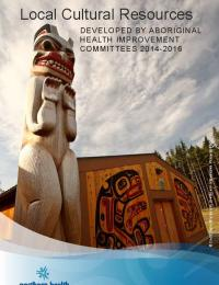 Totem pole beside a wood building with Indigenous art on the front