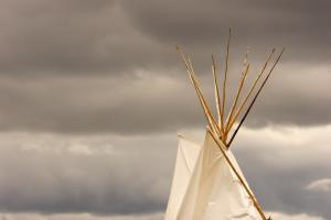 Top of a teepee against a grey sky