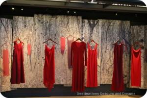 A series of red dresses hanging up in a display for the REDress Project