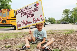 "Young boy sitting on the ground holding a sign that reads ""Equal Funding for First Nations Kids"""